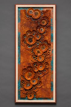 "'Ancient Tide Pools"" (32"" h x 13"" w). Carved Afzelia burl featuring 15 inset fossil ammonites. The sculpture rests on a patina copper sheet within a Maple/Bubinga frame. George Post, photography."
