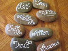 Piedras lisas con nombre para indicar el puesto de cada invitado