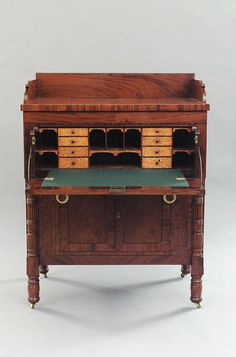 """An American Late Classical Mahogany Fall Front Secretary Desk, c. 1820, pencil-signed under top right document drawer """"... Clay of Kentucky"""", the shaped backsplash over projecting top and crossbanded frieze drawer enclosing a well-fitted interior of curly maple drawers, pigeon holes and the document compartment flanked by pilasters; the cupboard doors enclosing a shelf flanked by pilasters and carved, reeded and turned half columns, raised on turned legs, height 48 in., width 38 in."""