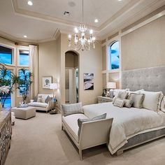Glam master bedroom. High ceiling, chandelier, large bay windows, and lounge area.