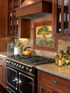 kitchen with paneled kitchen cabinets, leaded glass light fixtures, tile mural backsplash, simulated stone countertop, vintage range, classic craftsman green remodel