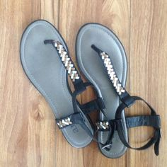 Sandals Silver and bronze accent colors with black straps. Straps are adjustable. Some normal wear and tear on the straps of the sandals. a.n.a Shoes Sandals