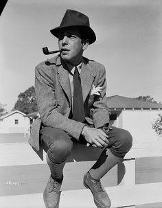 circa 1940:  American actor Humphrey Bogart (1899 - 1957) sitting on a fence smoking a pipe.