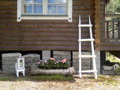 Vanhoista heinäseipäistä tehty tikapuut ja maalattu valkoisiksi ja koivunrunko kaiverrettu kukkapurkiksi...