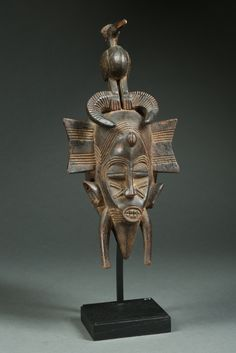 "Beautiful and Ornate Senufo Kpelliyee Mask with Bird (Parcours) -  This spectacular mask, with its clear, refined, natural features, is known as Kpeiliyee, or ""beautiful lady,"" and is danced by men who perform in female character. There are hundreds of variations of the Kpeiliyee masks, some smaller than face mask size, and others approximately the size of a larger, elongated facemask that extends just beyond the face of the dancer. The masks are danced with the piece affixed atop the…"