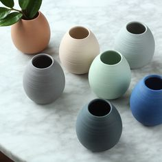 A gently tapered, tinted porcelain bud vase with hand carved lines that add texture to the unglazed porcelain exterior. Ceramics are made to order and will ship within 3 weeks of purchase. Dimensions: