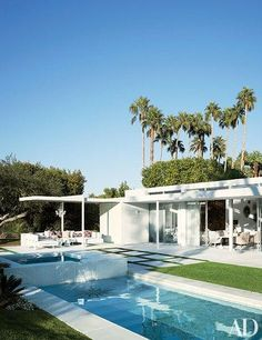 A crystal chandelier hangs above the chic outdoor living area at designer Emily Summers's 1960s Indian Wells home   archdigest.com