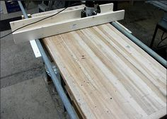 Great idea for a jig to flatten a slab of wood that won't fit in a planer.  Jig slides along pipes while the router does the cutting.