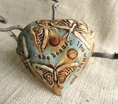 This Unique Ceramic Heart Wall Plaque is created with Butterflies and Circles. It is also stamped with the words  The beauty lies within. It can adorn a wall all by itself or as a grouping. You will truly love this piece as soon as you open they package!    -This is one of the large heart plaques that is glazed in Turquoise, Golden Yellow and Brown. Its pretty earthy so you will find divots, cracks, scratches and a possible hole, this is how it was intended to be made. -On the back you will…