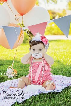 Super cute little girl celebrating her first birthday with a cake smash session! Love her pink pettiromper, homemade banner and matching balloons! Photo Credit: Ursula Carpenter