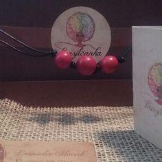 Colar feito com couro e sementes paxiubão vermelho.