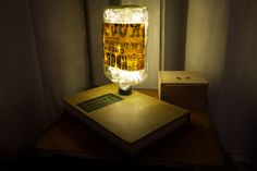 DIY lamp using an old book, an empty glass liquor bottle and a string of lights