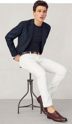 Man in navy sport coat over navy tee paired with white jeans.