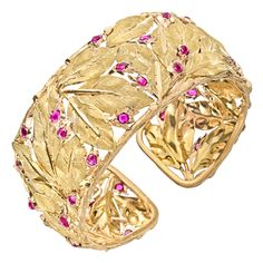 BUCCELLATI Gold  Ruby Leaf Cuff Bracelet. Oval-shaped, openwork leaf motif wide cuff bracelet, in hand-engraved 18k yellow gold, accented by circular-cut ruby accents, with hinge on one side. Italy. 21st Century