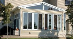 A traditional sunroom with glass wings under a shingled gable roof. #homeimprovement #sunroom
