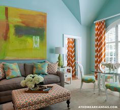 Tobi Fairley - Living room with vaulted ceiling over orange and green abstract art above modern taupe sofa beside Bungalow 5 Polo 1 Drawer Side Table topped with lime green lamp layered pillows paired with orange and blue ottoman used as coffee table.