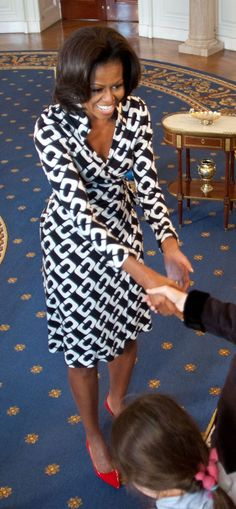 First Lady Michelle Obama looks absolutely incredible in a black and white wrap #DVF dress with red pumps.