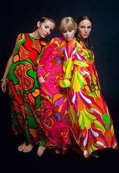 Psychedelic long dresses, Mademoiselle Magazine 1967. Three models stand close together wearing brightly colored maxi dresses; from left to right: sleeveless dress with swirl pattern in green, orange, red and black by Fifth Avenue Robes; a long...