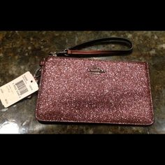 "Coach Glitter Wristlet  NWT Beautiful Coach glitter wristlet with adjustable strap.  Zip top closure, fabric lined interior, 2 id slots.  Color is Cherry Metallic.  Comes with Coach gift box and gift bag.  7"" x 4.25""   no trades Coach Bags Clutches & Wristlets"