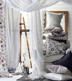 Romantische Collage aus weißen, grauen und geblümten Kissen, Gardinen, u. a. aus GULLDIS Meterware in Weiß, und Teppichen