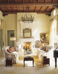 The Spanish Revival interiors of 1920s Florida architect Addison Mizner inspired this Austin living room. After studying photographs of Mizner's ceilings, designer Fern Santini and her team drew up patterns that were painted on the beams by two artists. Pale plaster walls highlight antiques like a 19th-century French chandelier and an 18th-century Italian mirror.    - HouseBeautiful.com