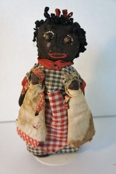 Sweet little black cloth doll holding two black nipple dolls