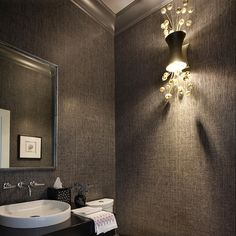 The masculine wallpaper pairs nicely with the playful and glamorous POP! Wall Sconce in this powder room by Daher Interior Designs. Dimmable, this sconce by Fisher Weisman is available in either white or yellow gold leaf options encircled in crystal spheres. Photo by Eric Roth.