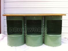 Our newest model of bars is a bit more conventional. Three upright 55 gallon steel drums with plenty of storage with its easy to reach elevated shelves. This sample is powder coated in an eye pleasing shade of green reminiscent of the Hamilton beach soda shop blenders. The top is North Carolina yellow pine and has many coats of wet sanded semi-gloss urethane. Additionally it has a tubular steel foot rest. Unit is 6 foot long and 28 inches wide.
