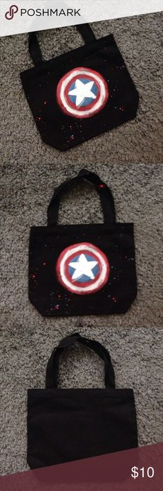Handmade Captain America 4th of July tote **won't be able to ship until next Friday**This little tote bag is one of a kind! Black with Captain America's shield and splattered red and blue, it's a super cute design! Perfect for trick or treating, or any other time you want to feel super! I love to do custom bundles!! 😊 Measurements 11''x9''x3'' Handmade Bags Totes