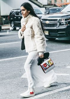A fur coat is paired with a sheer skirt, white Comme des Garcons x Converse shoes, and studded top handle bag