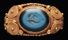 Ring, Roman,1st century AD. Gold with a blue stone carved with a dolphin. Note the delicate wire scrolls.