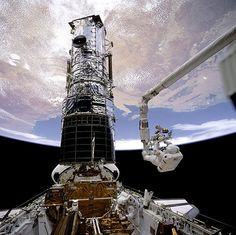 A photograph of astronauts repairing the Hubble space telescope, taken from the Endeavour space shuttle in 1993