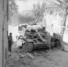 BRITISH ARMY ITALY 1944 (NA 18802) Object description Troops examining the wreck of a German PzKpfw IV tank knocked out in the village of San Savino, 19 September 1944.