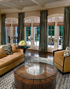 "Very well done windows with ""Roman shades"" in light brown and green floor length draperies. Lovely wooden center table and brown & blue/grey area rug, blend well with the tan and wood furniture and wooden floor. White beamed ceiling. A warm, inviting room."
