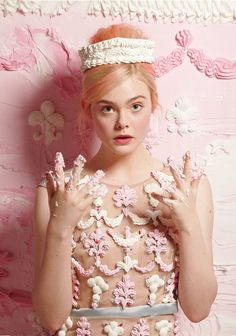 ELLE FANNING IN PRINT DEPICTING FROSTING / ON HER FINGERS / BEHIND HER / EVEN A FROSTING DRESS & CROWN