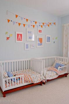 The orange and blue decor really makes this twin toddler bedroom pop! #twintoddlers #toddlerbedroom #twinsdecor