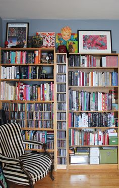floor to ceilings book shelves with a striped chair / in the home of jamie lawson & jacqui oakley
