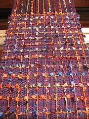Handwoven scarf currently on my loom. Variegated tencel yarn with novelty yarn as supplementary warp and weft.