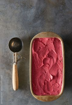 Tub of raspberry gelato with scoop