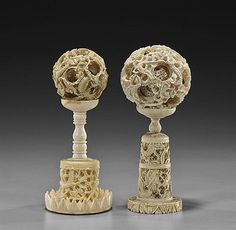 """Two early 20th Century Chinese carved ivory puzzle balls; both with openwork dragon motifs to the exterior: the larger with at least 9 inner concetric balls, the smaller with at least 5 inner concentric ball (damage to the interior of each), the ivory stands each with openwork dragon designs; H: 6 3/4"""" (taller, overall)"""