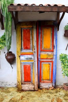 Mexican door. Orange, yellow and blue. Cactus at a side.