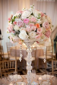 DIY tall centerpiece inspiration: Use E6000 glue to stack short dollar store glass candleholders onto each other to create a tall centerpiece stand. Glue to square mirrors for a stable base.  Add flowers and hanging crystals strands for the finishing touch! #DIY #wedding #decor