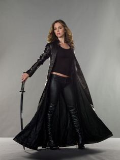 Elisha Dushku in Dollhouse - full length black leather coat jacket, black leather pants, black t-shirt, thigh high black leather boots