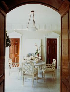 Rounded arch entry, neoclassical pediments framing wooden doors, and a quadrille take on traditional Chippendale dining chairs. Updated tradition.