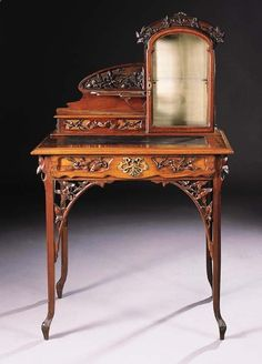A CARVED MAHOGANY DESK BY LEON BENOUVILLE – with glazed shelved compartment, open shelf and frieze drawers above rectangular top inset with leather writing surface, above frieze drawer on carved legs – 74cm. wide