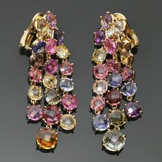 Bulgari Multicolor Sapphire Diamond Dangling Clip-on Earrings made in 18k yellow gold and prong-set with colorful round faceted sapphires in yellow, orange, pink, blue, green and brown tints, accented with round sparkling diamonds of an estimated 0.12 carats.