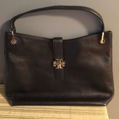 Black Tory Burch plaque handbag This bag is beautiful. Leather is soft and supple. You will definitely be noticed with this classy beautiful piece. It has plenty of room and inner compartments for storing your phone and credit cards. Never used.  Purchased at Nordstrom from 2015 Tory collection.  Minimal wear seen in pics likely happened at the store. Tory Burch Bags Shoulder Bags