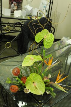 A fun tropical arrangement with anthurium, birds of paradise, and pin cushion protea.