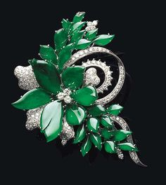 A JADEITE AND DIAMOND FLORAL BROOCH    Designed as a flowerhead composed of brilliant emerald green jadeite and pavé-set diamond petals with a diamond trefoil centre, extending sprays of matching jadeite leaves, further enhanced by a diamond-set scrolling ribbon and spray detail, mounted in 18K white gold, jadeite plaques with carved-in concave backs