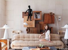 """Kelly Wearstler Home THE LIVING ROOM Wearstler relaxes on a low-slung vintage Tobia Scarpa sofa in a living room awash with sandy beiges and stony grays. """"It's all about texture and movement,"""" she says of the scheme. An oversize wooden artist's model sits on a 1970s geometric cabinet from JF Chen in Los Angeles."""